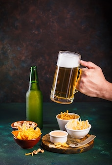 Glass mug with beer with foam and water drops and snacks on dark green