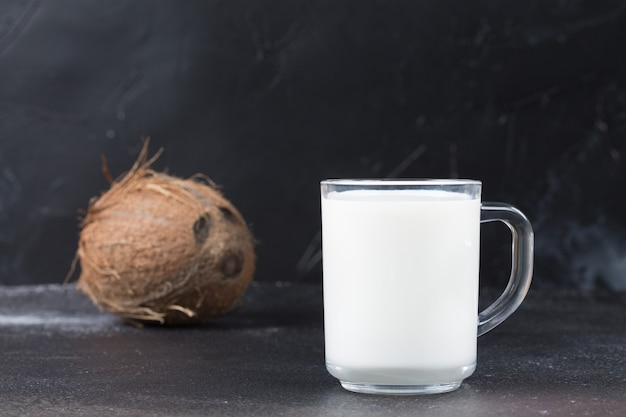A glass mug with coconut milk in the foreground. blurry black background. vegan