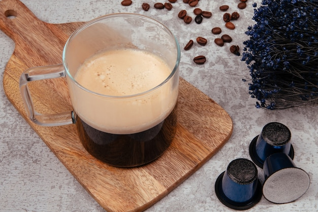 Glass mug with coffee and coffee capsules