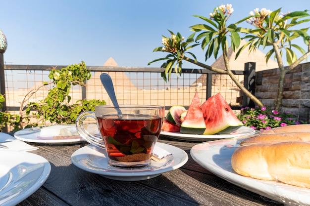 エジプトの主要なアトラクション、ギザの大ピラミッドの美しい背景にお茶を入れたガラスのマグカップ。