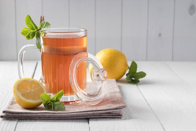 Стеклянная кружка с вкусной чайной ложкой на белом деревянном столе