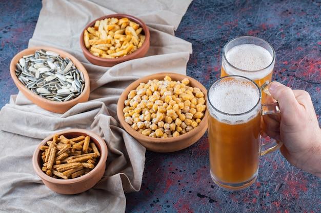 Boccali di birra in vetro con pangrattato essiccato su una superficie scura