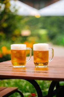 カフェテラスのテーブルにビールのガラスのマグカップ