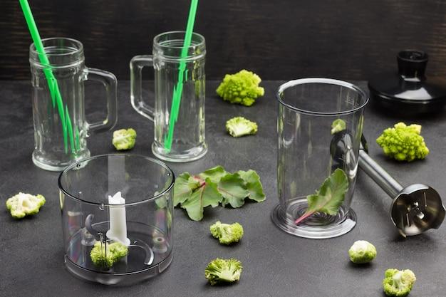 ブロッコリーの葉と緑のストローが付いたガラスのマグカップ。