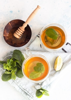 Glass mugs with traditional moroccan mint tea with honey and lime