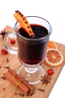Glass of mulled wine and ingredients on a wooden table isolated on white background