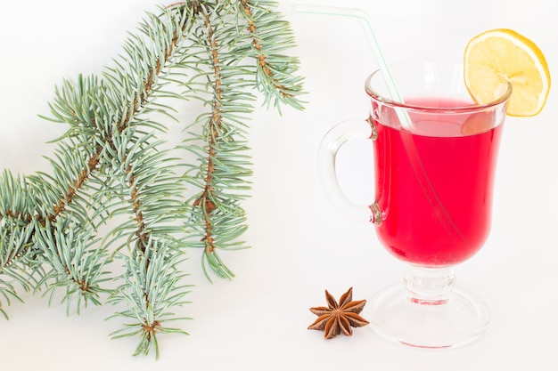 A glass of mulled wine and a slice of lemon, star anise and fir branch on a white background