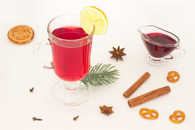 A glass of mulled wine and a slice of lemon, star anise  on a white background