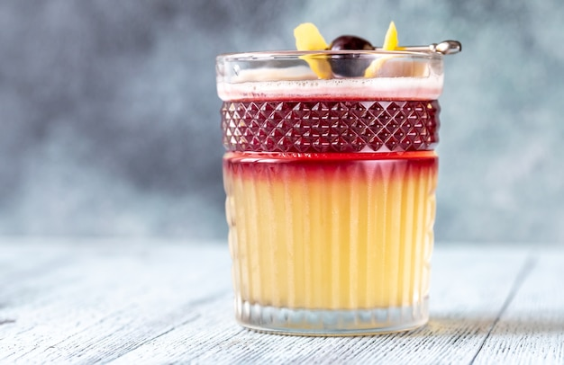 Glass of new york sour garnished with cocktail cherry and lemon peel
