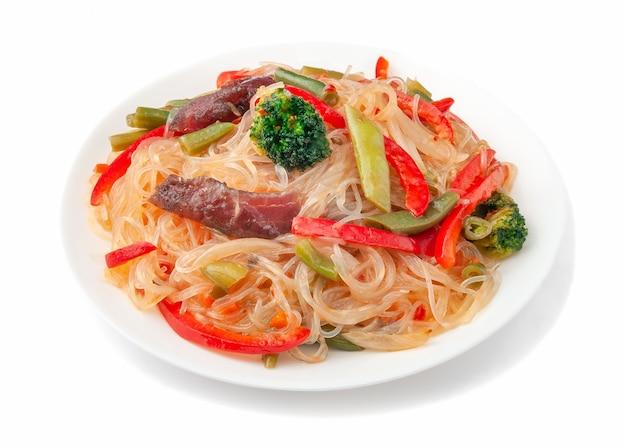 쇠고기, 양파, 녹두, 파프리카, 브로콜리, 새콤한 소스, 오이를 곁들인 유리 국수. 하얀 접시에. 흰색 배경. 위에서 보기를 분리합니다.