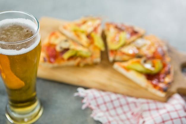 Стакан пива с кусочками пиццы на заднем плане