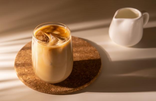 크림 우유와 함께 아이스 커피 한 잔 얼음으로 콜드 브루 커피 음료 이른 아침 태양 빛