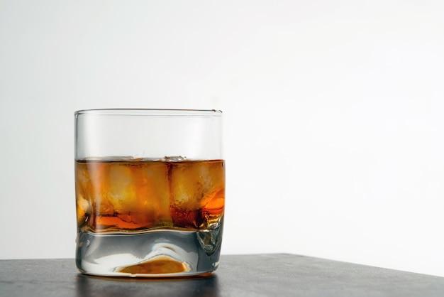 Стакан выдержанного золотого виски с кубиками льда на столе.