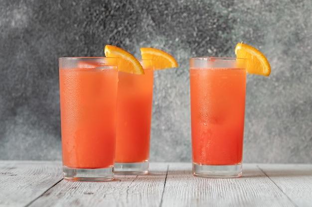 オレンジウェッジを添えたアラバマスラマーカクテルのグラス