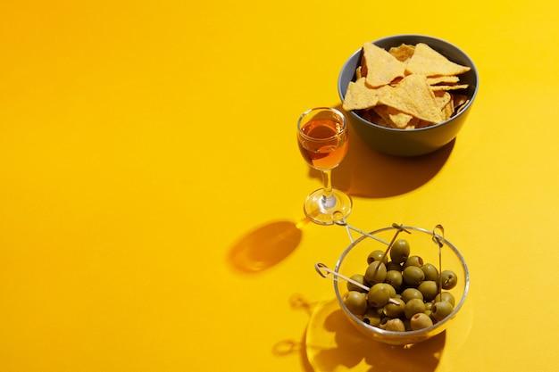 コピースペースのある黄色のガラスボウルにグリーンオリーブを入れたアルコールとナチョスのグラス