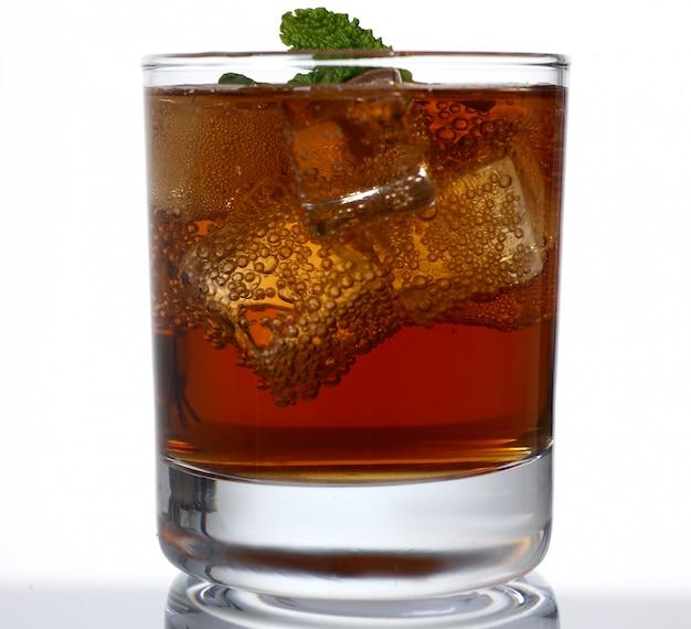 Стакан алкогольного напитка со льдом в студии