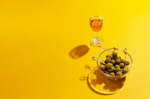 コピースペースのある黄色のガラスボウルにグリーンオリーブを入れたアルコールのグラス