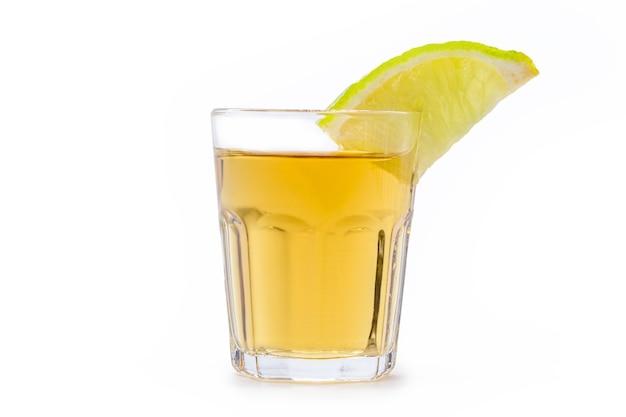 孤立した白い背景に、ブラジルで「pinga」または「cachaã§a」と呼ばれるサトウキビから蒸留されたレモン入りアルコール飲料のガラス
