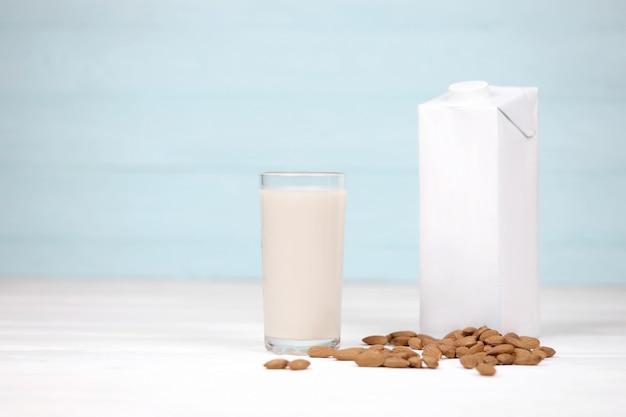 흰색 나무 테이블에 캔버스 원단에 아몬드 견과류와 아몬드 우유의 유리. 해독, 건강한 식습관 및 다이어트를위한 유제품 대체 우유. 선택적 초점