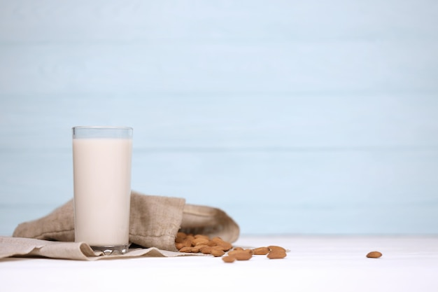 흰색 나무 테이블에 캔버스 원단에 아몬드 견과류와 아몬드 우유의 유리. 해독을위한 유제품 대체 우유