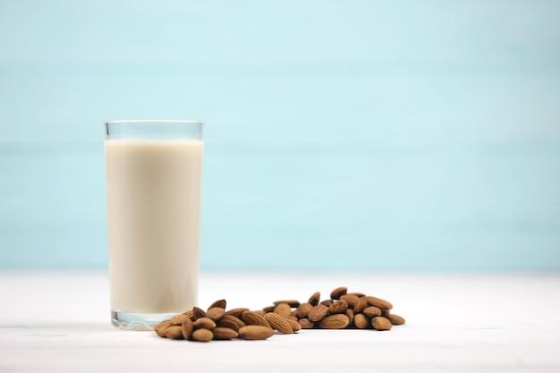 흰색 나무 테이블에 아몬드 견과류와 아몬드 우유의 유리. 해독을위한 유제품 대체 우유