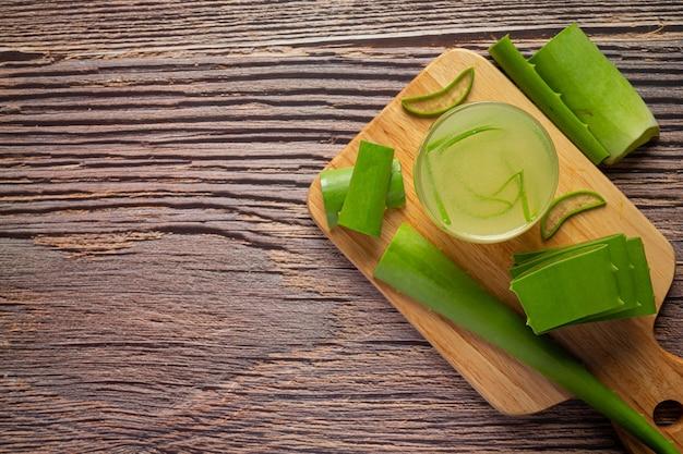 木製のまな板に置かれたアロエベラジュースのガラス
