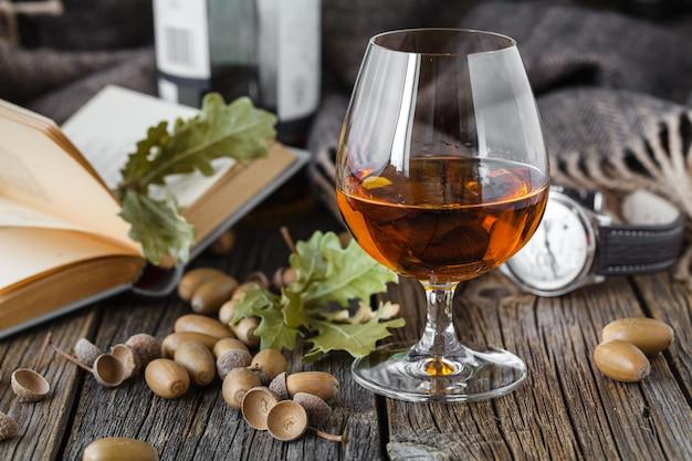 Стакан виски янтарного цвета в бокале на дубовом столе