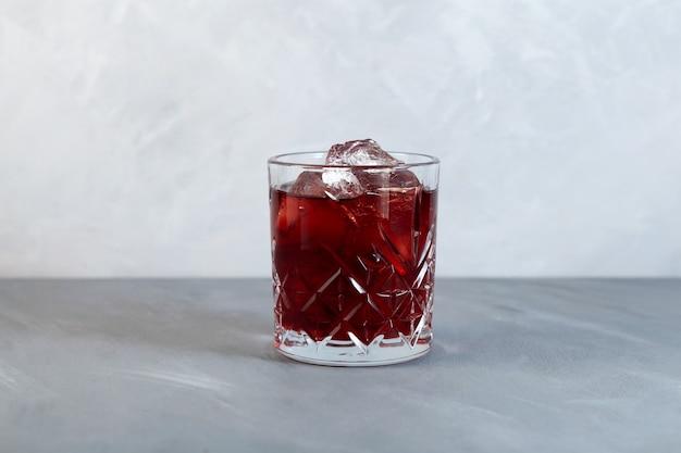 赤いベルモットの苦いソーダ水と角氷とアメリカーノアルコールカクテルのガラス