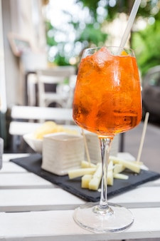 レストランの有名なさわやかな飲み物イタリアのテーブルの上のアペロールスプリッツカクテルのグラス