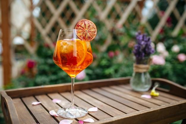 Стакан коктейля aperole spritz, украшенный долькой апельсина на подносе с водой
