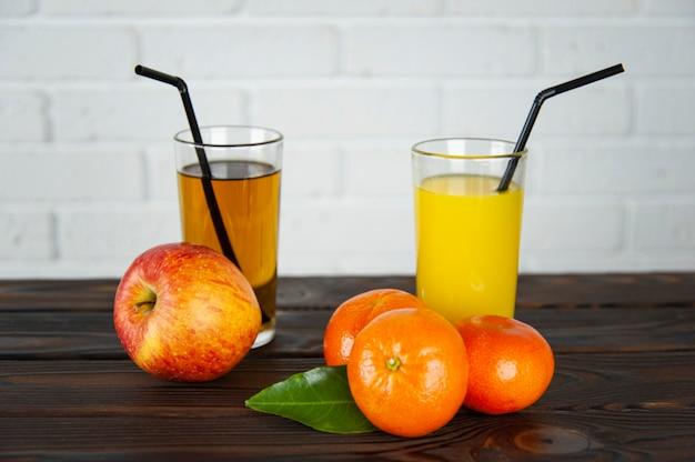 Стакан яблочного и апельсинового сока с яблоками и апельсинами на столе