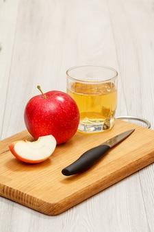빨간 사과, 얇게 썬 것, 나무 커팅 보드에 칼을 넣은 사과 주스 한 잔.