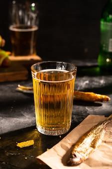黒いテーブルの上のビールと魚のガラス