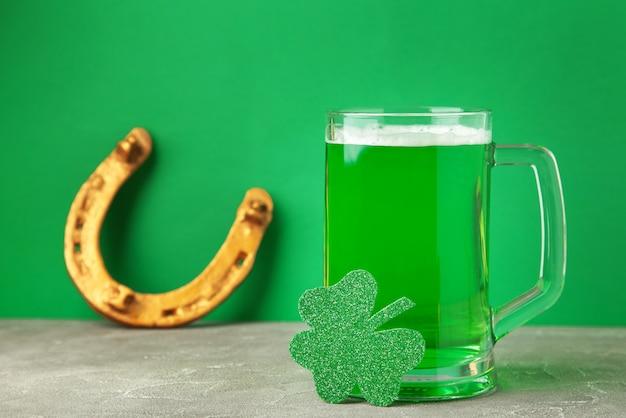 녹색 벽에 세인트 패트릭의 날 맥주와 말굽의 유리. 평면도.