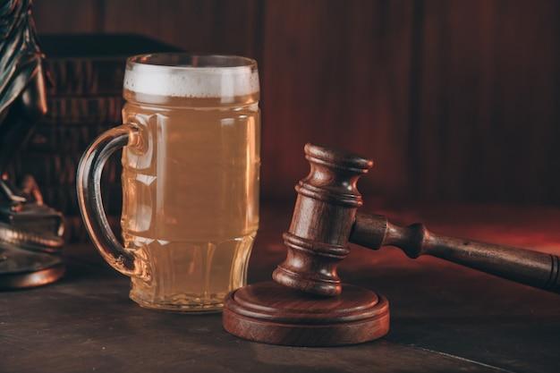 나무 테이블에 법률의 상징으로 맥주와 판사 망치의 유리