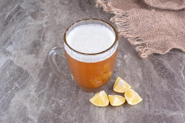 大理石の表面にビールとレモンのスライスのガラス