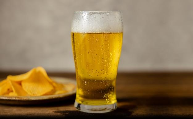 テーブルの上にビールとポテトチップスのプレートのガラス。自宅やカフェでビールを飲む