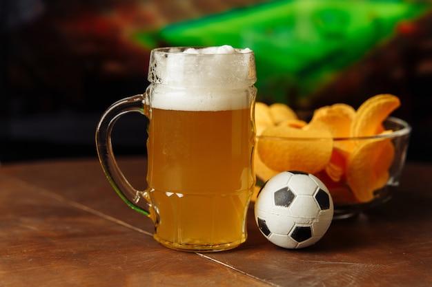 フットボールの試合のテレビの背景にビールと軽食のグラス