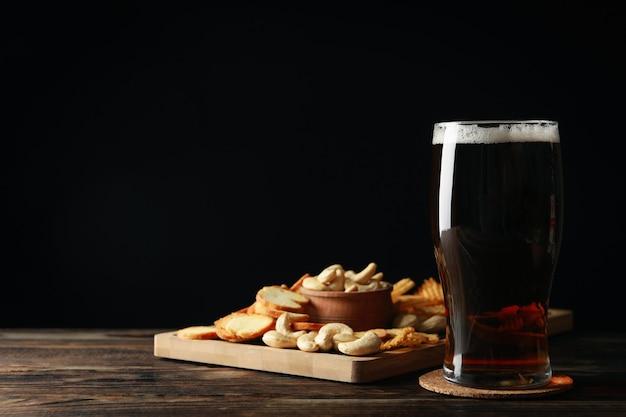 Стакан пива и закусок на деревянном столе