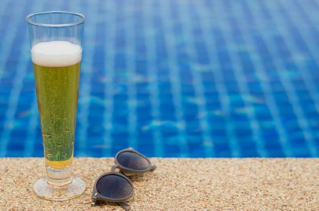 スイミングプールの横にあるビールとサングラス