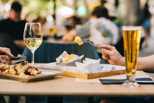Бокал пива и вина на столе ест еду на террасе - две девушки вместе обедают в ресторане
