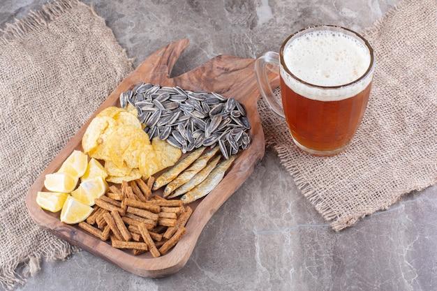 ビールのグラスと軽食の木の板。高品質の写真