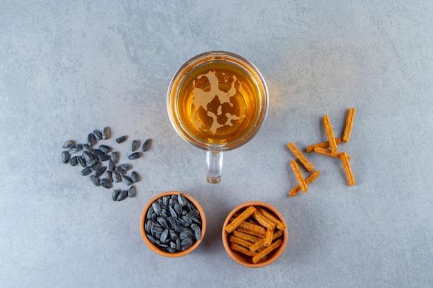Стакан пива, миска семян и гренки на мраморной поверхности.