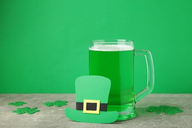 緑の背景に聖パトリックの日のビールのグラス。上面図。