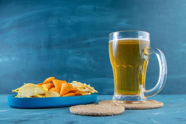 Стакан пива на подставке рядом с различными чипсами в деревянной тарелке на синем фоне.
