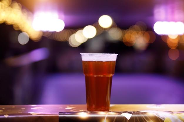 Стакан пива на концертных огнях.
