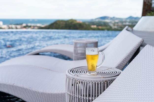 街と海の景色、ホアヒン、タイの屋上スイミングプールでビールのグラス。