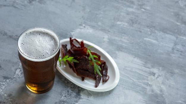 石のテーブルとレンガの上のビールのガラス