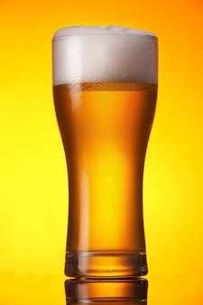 オレンジ色の背景の上のビールのガラス