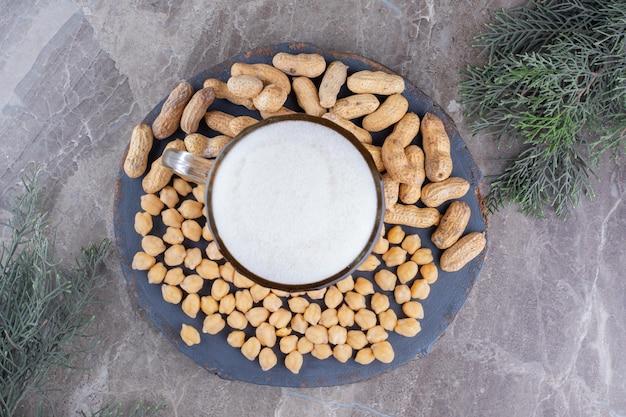 木片にビール、エンドウ豆、ピーナッツのグラス。高品質の写真